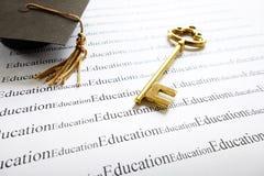 Success keys. Closeup of a gold key and graduation cap, on Education text Stock Photos