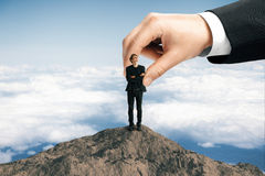 Success and leadership concept. Huge businessman hand placing young businessman on mountain top. Sky background. Success and leadership concept Stock Photography
