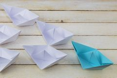 Success, leadership concept. Leadership concept with blue paper ship on wood Royalty Free Stock Image