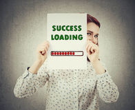 Success loading bar. Businesswoman, with a happy emotion, hiding face behind a white paper with a loading bar symbolizing business success load percentage,  on Royalty Free Stock Images