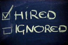Success in looking for a job: hired, not ignored. Chalk writings on blackboard, hired vs; ignored in a recruiting process Stock Photo
