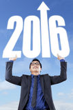 Success man lifting numbers 2016. Portrait of male entrepreneur lifting numbers 2016 with upward arrow under blue sky Stock Images