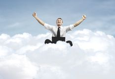 Success of man sitting on a cloud. Businessman admiring his success in cloud Stock Images