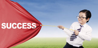 Success is mine. A little businessman pulling a banner of success Royalty Free Stock Photos