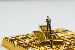 Success miniature rich businessman standing on stack of gold bar, bullion or ingot using as wealth management, gold investment and. Financial asset royalty free stock photo