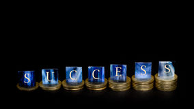 Success. Mosaic tiles and coins in front of black background - Concept of success Stock Image