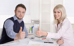 Success at office: two colleagues with thumps up at desk. Stock Photo