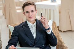 Success and persistence. Confident and successful businessman si. Tting in office and holding a cell phone looking at the camera and smiling while drinking Stock Photos