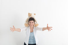 Success positive emotions. Happy young woman in white shirt stretching hands ahead, wanting to hug someone. Plush cat. Sits on her neck Royalty Free Stock Photography