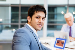 Success and professionalism in person. Businessman in office smiling at camera stock photography