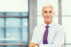 Success and professionalism in person. Businessman standing in office smiling at camera stock photo