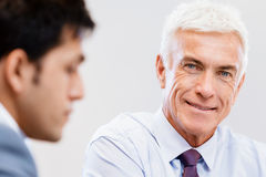 Success and professionalism in person. Businessman standing in office smiling at camera stock images