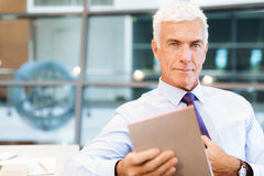 Success and professionalism in person. Businessman standing in office smiling at camera royalty free stock photography