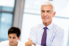 Success and professionalism in person. Businessman standing in office smiling at camera royalty free stock images
