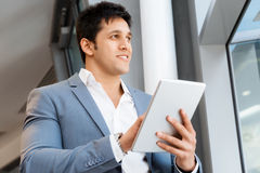 Success and professionalism in person. Businessman standing with tablet smiling at camera stock photo