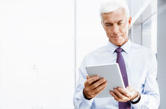 Success and professionalism in person. Businessman standing with tablet smiling at camera stock photos