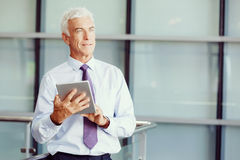 Success and professionalism in person. Businessman standing with tablet smiling at camera royalty free stock photography
