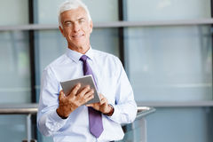 Success and professionalism in person. Businessman standing with tablet smiling at camera royalty free stock images