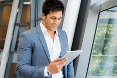 Success and professionalism in person. Businessman standing with tablet smiling at camera royalty free stock image