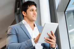 Success and professionalism in person. Businessman standing with tablet smiling at camera royalty free stock photos
