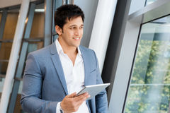 Success and professionalism in person. Businessman standing with tablet smiling at camera stock image
