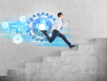 Success and progress concept. With running businessman and digital cogwheel trail on concrete background Stock Image