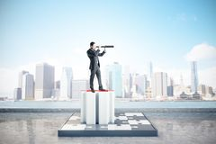 Success, quiz and future concept. Businessman with telescope looking into the distance on abstract jigsaw pedestal on blurry bright city background. Success royalty free stock image
