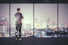 Success and research concept. Back view of thoughtful young businessman standing in modern business interior with Bangkok city view. Success and research concept stock photos