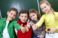 Success in school. Group of four classmates showing sign of ok Royalty Free Stock Photo