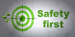 Security concept: target and Safety First on wall background. Success security concept: arrows hitting the center of target, Green Safety First on wall Royalty Free Stock Photography