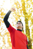 Success in sport. Handsome sportsman celebrating victory raising his arm and fist with sun behind. Outdoors scene in park with blur trees and nature on Stock Photos