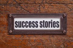 Success stories label. Success stories - file cabinet label, bronze holder against grunge and scratched wood Stock Image