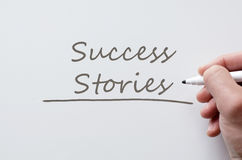 Success stories written on whiteboard. Human hand writing success stories on whiteboard Royalty Free Stock Photo