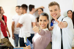 Success students. Success couple  students showing thumbs up with a group of students at the background Stock Photo