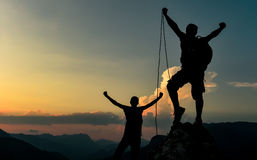 Success of the summit climb rope. He makes friends with mountain activities .Outdoor activities.Mountaineering and peacefull concept stock images