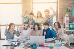 Success and team work concept. Group of business partners with r. Aised up hands in light modern workstation, celebrating the breakthrough in their company royalty free stock image