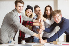 Success and teamwork concept. Attractive young people at workplace stacking hands, showing thumbs up. Success and teamwork concept Royalty Free Stock Photo