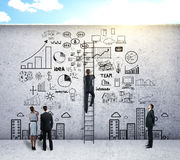 Success and teamwork concept. Back view of businesspeople climbing ladder and looking at creative business sketch on concrete wall. Success and teamwork concept Royalty Free Stock Image