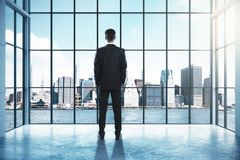 Success and think concept. Back view of young businessman looking out of window in interior with city view. Success and think concept. 3D Rendering Royalty Free Stock Photos