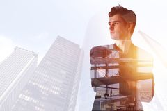 Success and think concept. Thoughtful young businessman standing on abstract creative city office background with sunlight and copy space. Double exposure royalty free stock images
