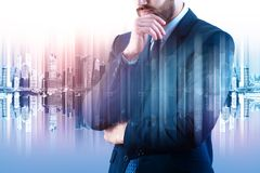 Success and think concept. Thoughtful young businessman on abstract blurry city background. Double exposure royalty free stock photo