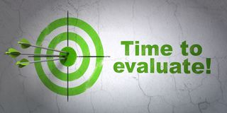 Time concept: target and Time to Evaluate! on wall background Stock Photo