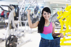 Success to lose weight. Happy Asian woman shows her old huge pair of jeans. Weight loss concept, shot in fitness center Royalty Free Stock Photo