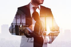 Success and tomorrow concept. Thoughtful young businessman standing on abstract creative city office background with sunlight and copy space. Double exposure Stock Images