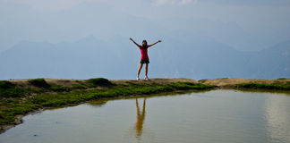 Success. A tourist celebrating a Success victory on top of a mountain next to a puddle Royalty Free Stock Photography