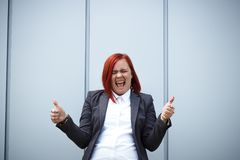 Success! Victory! Happy Successful Red-haired Girl Boss, Businesswoman In A Suit Emotionally Celebrates, With Space For Text And Royalty Free Stock Photos