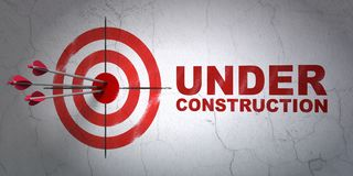 Web design concept: target and Under Construction on wall background. Success web design concept: arrows hitting the center of target, Red Under Construction on Royalty Free Stock Photo