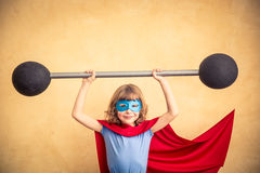 Success and winner concept. Superhero child against grunge wall background. Kid holding a barbell. Success and winner concept Royalty Free Stock Image