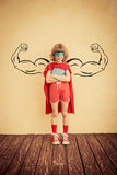 Success and winner concept. Superhero child with drawn muscles against grunge wall background. Success and winner concept Stock Photography
