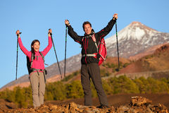 Success winning celebrating hiking people at top. Cheering hiker couple enjoying freedom on hike with arms raised in mountain landscape. Woman and men on Royalty Free Stock Images